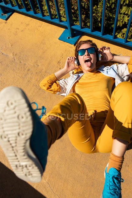 From above chilling teen in sunglasses listening to music with headphones while lying on vivid pavement with blue fence — Stock Photo