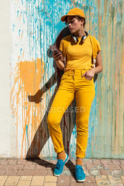 Stylish millennial in bright yellow outfit with headphones and smartphone standing against wall with colorful paint drips — Stock Photo