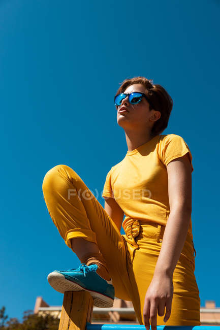 From below trendy teenager in sunglasses and stylish yellow clothes sitting on crossbar against clear blue sky — Stock Photo