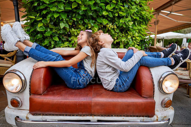 Seitenansicht von Kindern, die Rücken an Rücken sitzen und die Beine nach oben auf die zur Couch umfunktionierte Autofront legen und nach oben zur Decke schauen — Stockfoto