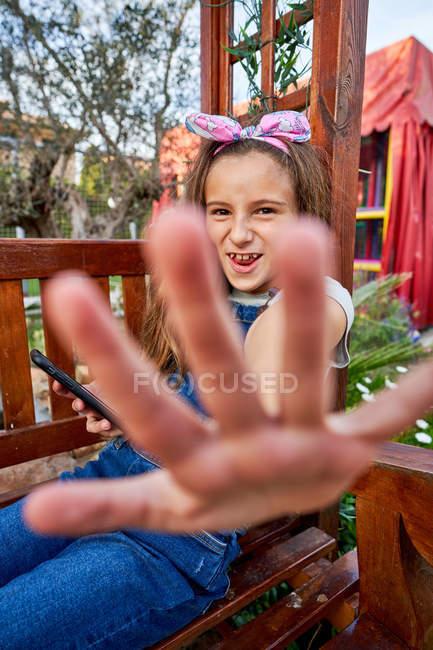 Позитивная девушка сидит на детской площадке и болтает в социальных сетях со смартфона, делая стоп-жест в попытке скрыть свои секреты — стоковое фото