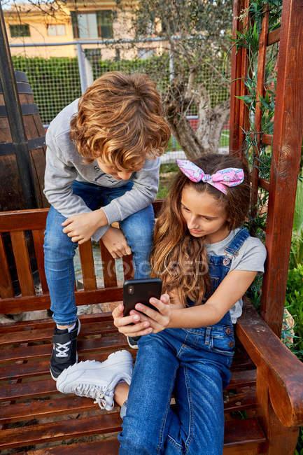 Menina mostrando algo no smartphone para irmão — Fotografia de Stock