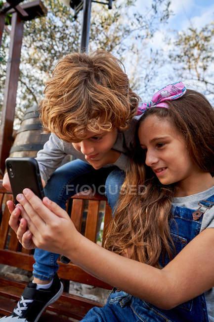 Jovem sorridente menina segurando smartphone enquanto preocupado menino sentado no banco de volta e navegar na Internet no fundo com parque — Fotografia de Stock