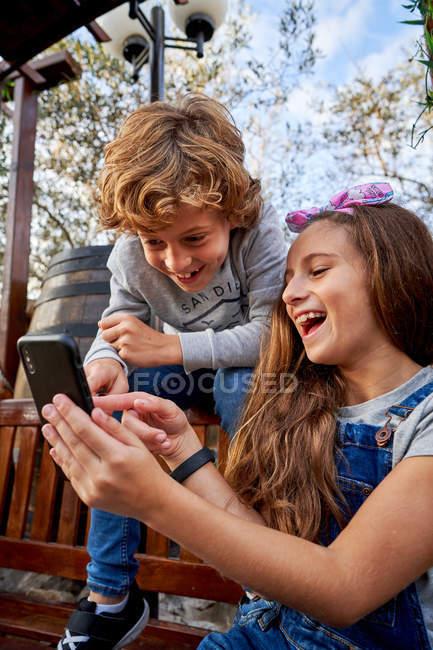 Fille montrant quelque chose sur smartphone à frère — Photo de stock