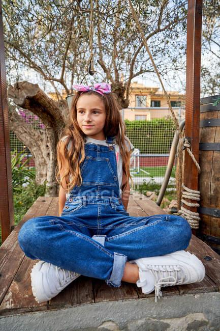 Lächelndes unschuldiges Mädchen sitzt im Hinterhof des Hauses — Stockfoto