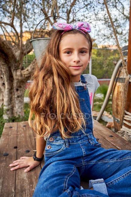 Smiling innocent girl sitting in house backyard — Stock Photo