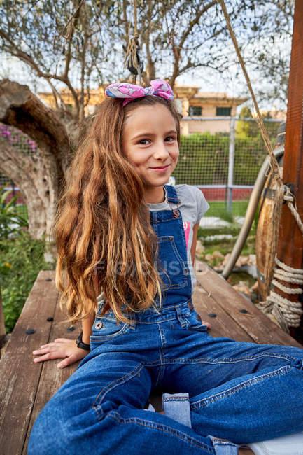 Joven chica pelirroja feliz sentado con las piernas cruzadas en el banco de madera mientras se apoya en los brazos y mirando a la cámara en el día de verano brillante - foto de stock