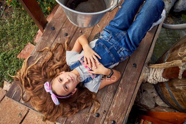 Lächelndes unschuldiges Mädchen liegt im Hinterhof des Hauses — Stockfoto