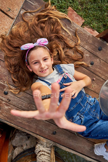 Sonriendo inocente chica acostada en casa patio trasero - foto de stock