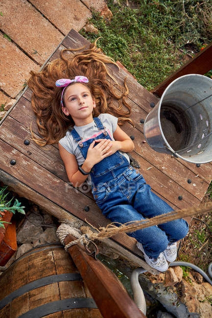 Smiling innocent girl lying in house backyard — Stock Photo