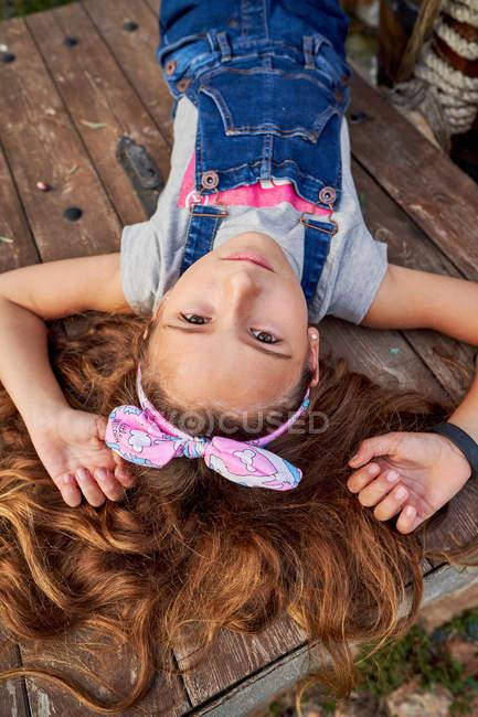 Улыбающаяся невинная девушка лежит на заднем дворе дома — стоковое фото