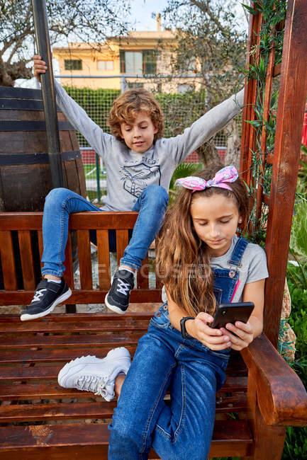 Ragazza utilizzando smartphone vicino fratello — Foto stock