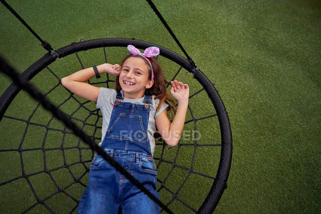 Von oben niedliche unbeschwerte weibliche Kind in Jeans-Overall auf schwarzen Spinnennetz Baumschaukel liegend und Blick in die Kamera auf dem Hintergrund mit grünem Cover — Stockfoto