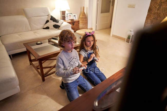 Діти грають вдома у відеоігри для консолей. — стокове фото