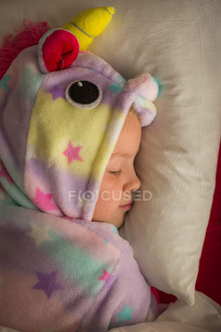 Ragazza in pigiama unicorno dormire a letto a casa — Foto stock