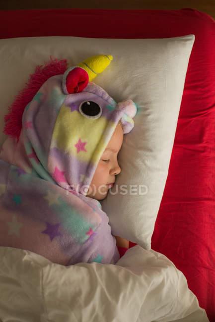 Grazioso bimbo in coloratissimo pigiama unicorno kigurumi ricoperto di coperta che dorme a letto con biancheria da letto bianca e rossa — Foto stock
