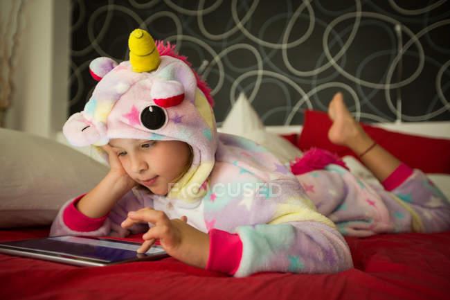 Mädchen im Einhorn-Pyjama mit Tablette im Bett — Stockfoto