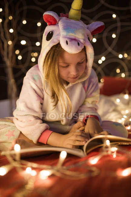 Little cute girl reading book in bedroom decorated with Christmas lights — Stock Photo