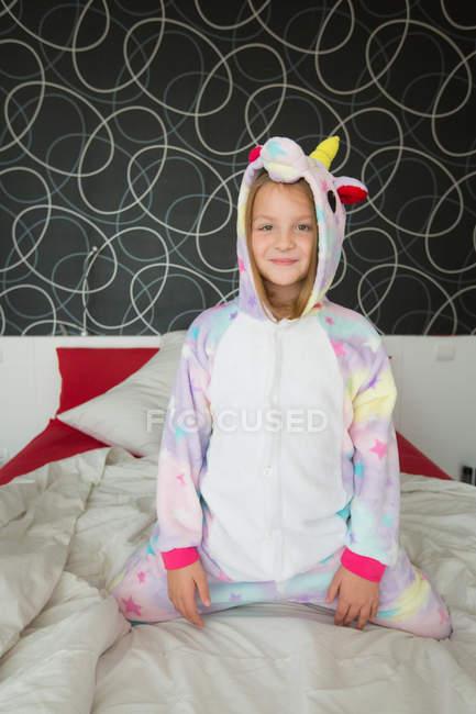 Fille gaie en pyjama licorne assis et regardant à la caméra sur le lit — Photo de stock