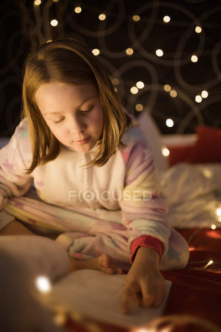 Girl reading book in bedroom decorated with Christmas lights — Stock Photo