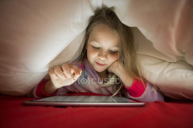 Mignonne petite fille blonde en pyjama en utilisant la tablette tout en étant couché sous la couverture dans le lit la nuit — Photo de stock