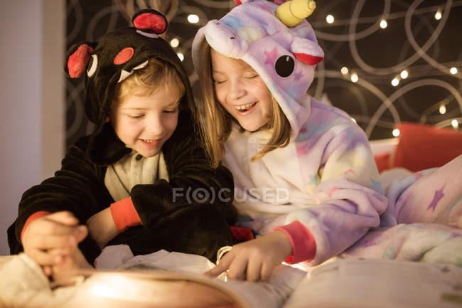 Дети читают рождественские сказки в постели на Рождество — стоковое фото