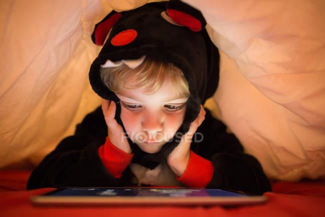 Menino pré-escolar usando tablet sob cobertor na cama — Fotografia de Stock