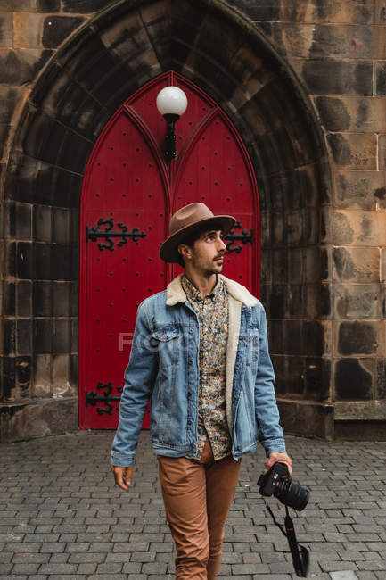 Calm photographer in hat strolling with camera on cobblestone street against red door of old building in Scotland — Stock Photo