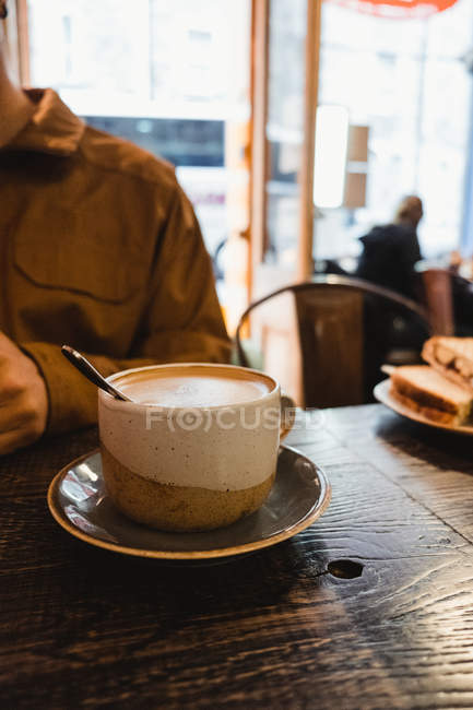Cropped of person sitting at table with ceramic cup of delicious aromatic latte while breakfast in modern cafe in Scotland — Stock Photo