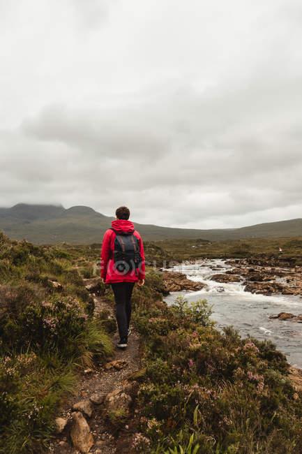 Visão traseira do homem com mochila caminhando ao longo da trilha perto do rio montanha em pastagens contra terras altas nebulosas da Escócia — Fotografia de Stock