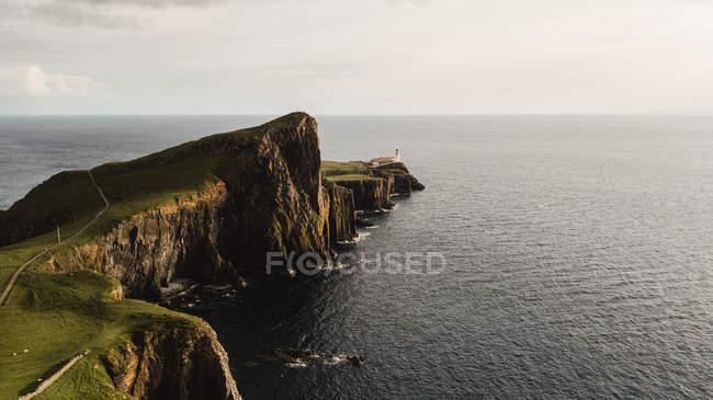 Dall'alto meraviglioso scenario di strada che conduce attraverso la costa rocciosa al faro contro tranquillo paesaggio marino in Scozia — Foto stock