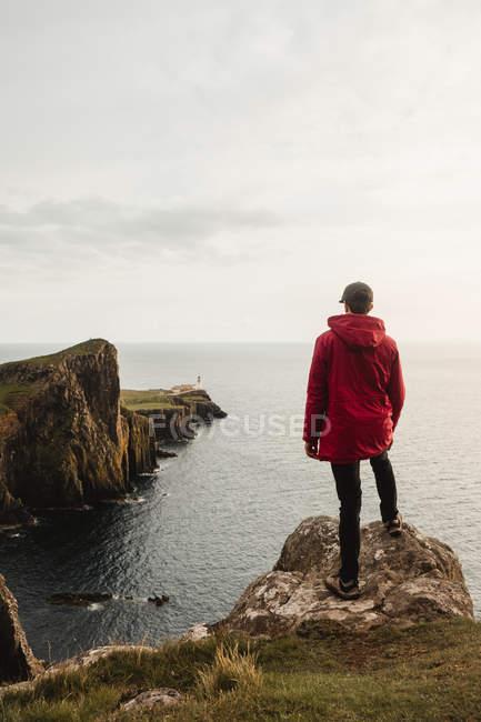 Touriste solitaire debout sur la côte rocheuse contre de l'eau de mer tranquille sous un ciel gris en Écosse — Photo de stock
