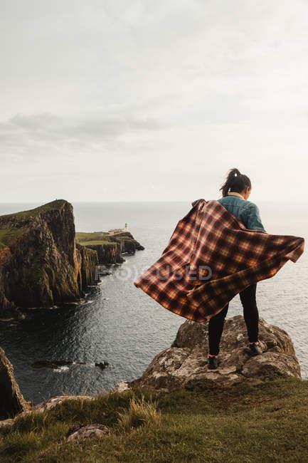 Vista posteriore di donna solitaria con plaid a scacchi in piedi sulle scogliere e guardando in basso il paesaggio marino in Scozia — Foto stock