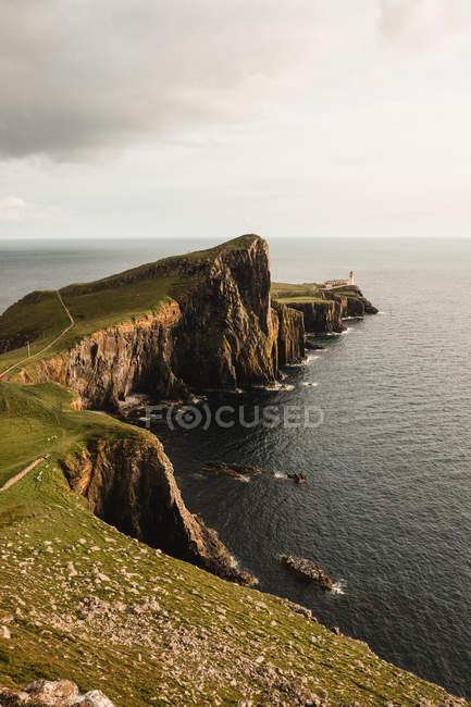 Скалистое побережье среди спокойной морской воды в солнечное время дня в Шотландии — стоковое фото