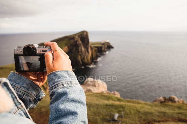 Cropped of person taking photo with camera of beautiful scenery of rocky headland against calm sea waves in Scotland — Stock Photo