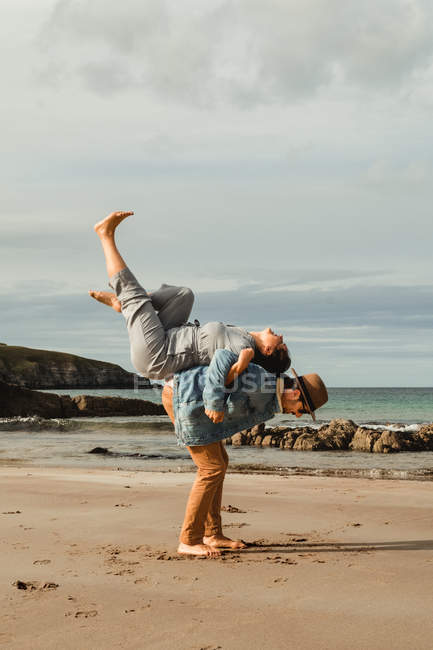Side view of man holding on back laughing woman with raised legs on sandy beach with rocks on cloudy day in Scotland. — Photo de stock