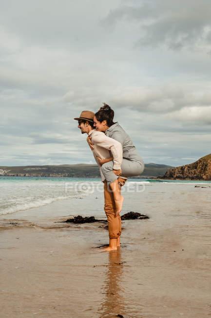 Happy man giving woman piggyback ride on Scottish sandy coast — Stock Photo