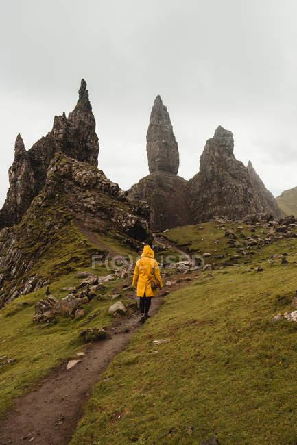 Rückansicht einer Person in gelbem Mantel, die auf einem Fußweg auf grünen Hügeln vor nebligen Felsen des alten Mannes von Storr in Schottland wandelt — Stockfoto