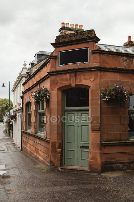 Vintage red brick building with green door and empty space for shop sign decorated with flowers on street of Scotland — Stock Photo