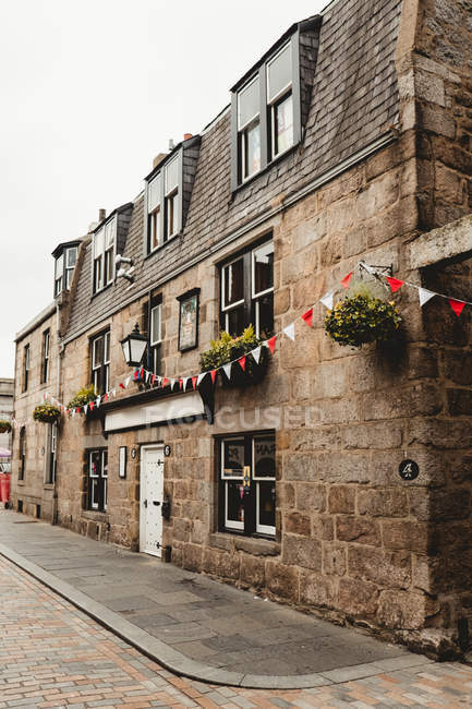 Old stone building with brown walls and lantern over door decorated with garland of red and white flags in Scottish city — Stock Photo