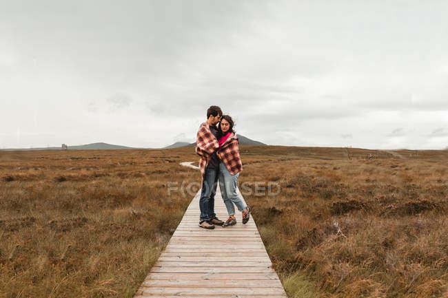 Ein paar Reisende im Karo stehen an trüben Tagen auf einem Holzweg zwischen braunem Moor in Schottland — Stockfoto