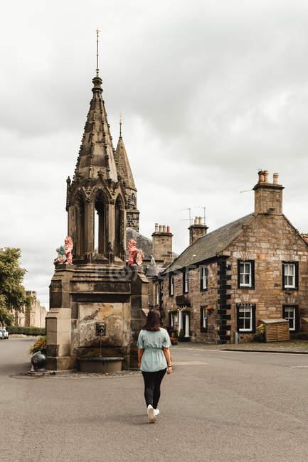 Vista trasera de las mujeres que viajan caminando por la plaza del casco antiguo, con hermosas fuentes medievales y edificios de piedra en Escocia. - foto de stock