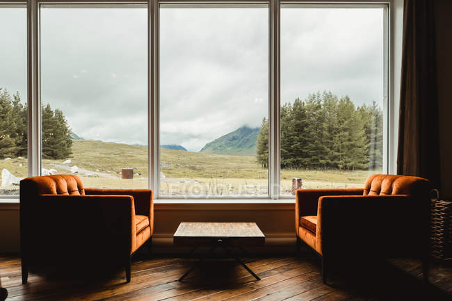 Scenic landscape view from wide window of Scottish country hotel lounge with table and sofas — Stock Photo