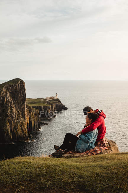 Side view of couple of tourists sitting on cliffs and embracing while enjoying peaceful scenic landscape during travel at Scotland — Stock Photo