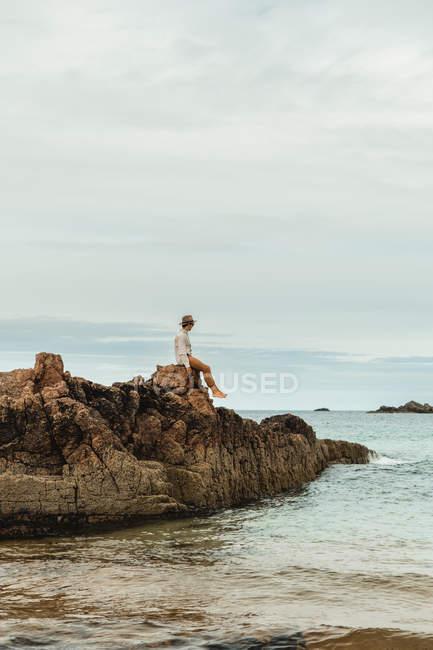 Einsamer Tourist sitzt an felsiger Küste vor ruhigem Meerwasser unter grauem Himmel — Stockfoto