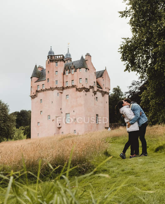 Side view of happy embracing couple standing on green hills next to medieval castle during tour to Scotland — Stock Photo