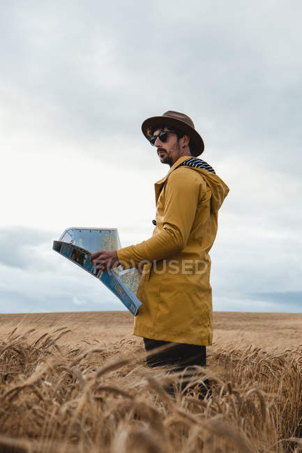Traveler with map standing in field in Scotland — Stock Photo