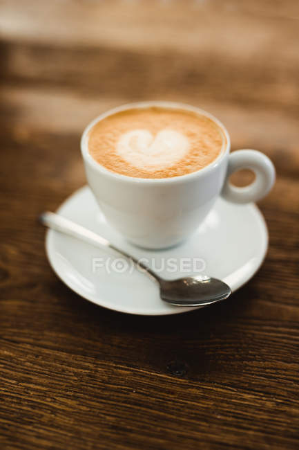 Cup of fresh cappuccino with heart shape on froth served on wooden table in cafe — Stock Photo