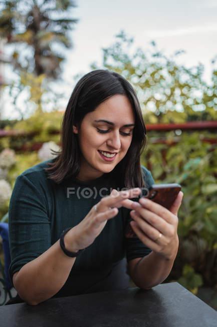 Jovem morena em roupas casuais navegando smartphone e rindo enquanto descansa no terraço com plantas verdes — Fotografia de Stock