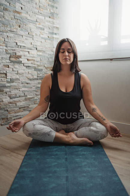 Молодая женщина, сидящая в позе лотоса на коврике для йоги и занимающаяся утренней йогой дома — стоковое фото